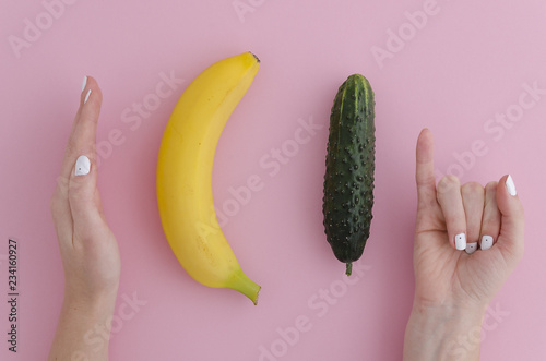 Foto Girl jokingly measures the size of a banana and cucumber comparing with the man dick long or large size