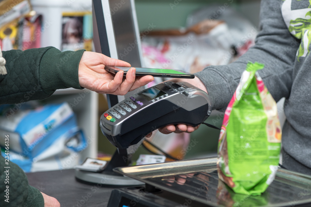 Fototapeta Contactless payment using smartphone and electronic payment terminal in store. NFC and paypass