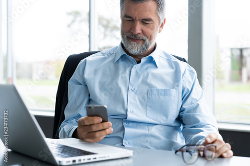 Fototapeta Mature business man in formal clothing using mobile phone. Serious businessman using smartphone at work. Manager in suit using cellphone in a modern office. obraz