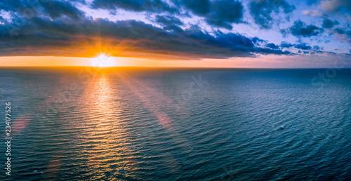 Fototapeta Lonely boat in wast ocean at sunset - wide aerial panorama obraz