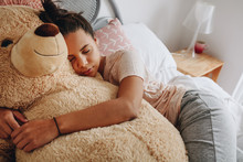 Girl Sleeping On Bed Holding A...