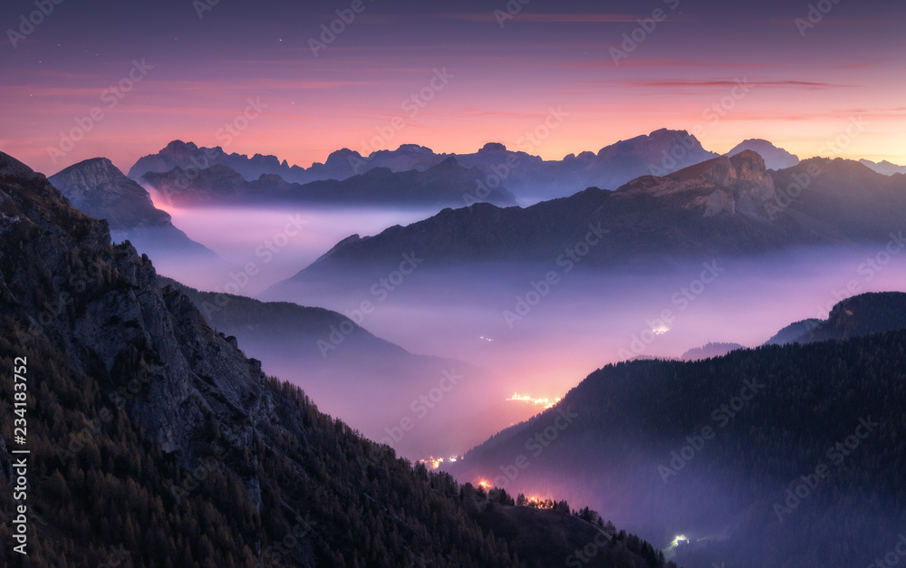 Fototapety, obrazy: Mountains in fog at beautiful night in autumn in Dolomites, Italy. Landscape with alpine mountain valley, low clouds, forest, purple sky with stars, city illumination at sunset. Aerial. Passo Giau