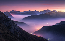 Mountains In Fog At Beautiful Night In Autumn In Dolomites, Italy. Landscape With Alpine Mountain Valley, Low Clouds, Forest, Purple Sky With Stars, City Illumination At Sunset. Aerial. Passo Giau