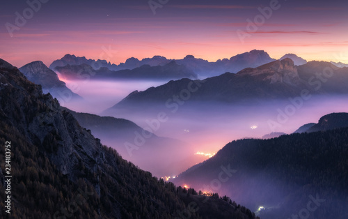 Papiers peints Aubergine Mountains in fog at beautiful night in autumn in Dolomites, Italy. Landscape with alpine mountain valley, low clouds, forest, purple sky with stars, city illumination at sunset. Aerial. Passo Giau