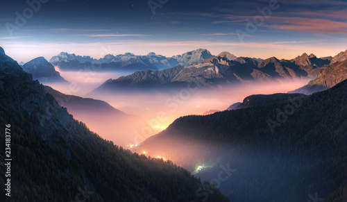 Mountains in fog at beautiful night in autumn in Dolomites, Italy. Landscape with alpine mountain valley, low clouds, forest, colorful sky with stars, city illumination at dusk. Aerial. Passo Giau