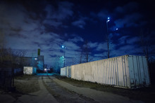 Eerie Industrial Urban Street City Night Scene With Truck Cargo Freight Shipping Containers, Train Railroad Tracks, Vintage Factory Warehouses, And The Moon.
