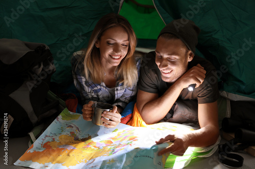 Young couple in sleeping bags with map and flashlight inside of tent