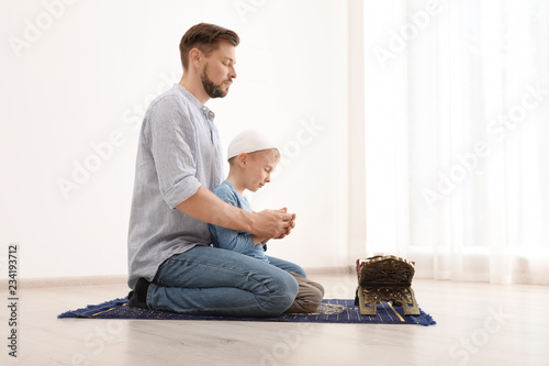 Muslim man and his son praying together indoors. Space for text