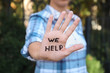 """canvas print picture - Woman showing hand with words """"WE HELP"""" outdoors, closeup"""