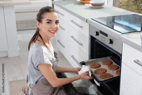 Young woman taking baking sheet with cookies from oven in kitchen