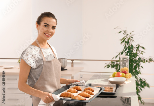 Young woman holding oven sheet with homemade croissants in kitchen