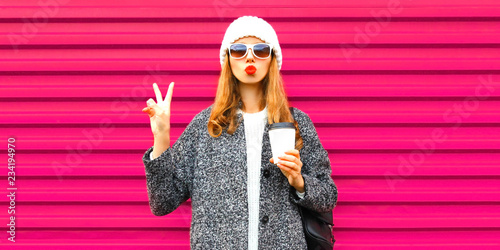 obraz PCV Fashion and people concept - cool stylish woman blowing red lips sends an air kiss on colorful pink wall background