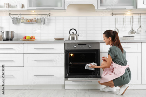 Young woman baking something in oven at home