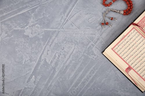 Muslim prayer beads, Quran and space for text on grey background, top view