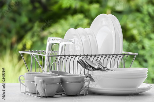 Set of clean dishware on table against blurred background