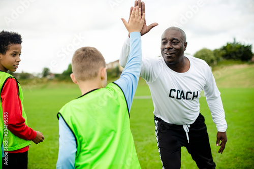 Photo Football coach doing a high five with his student