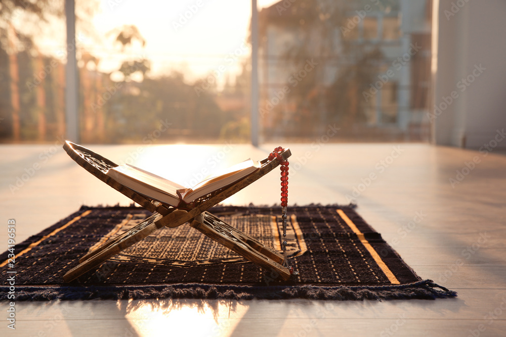 Fototapety, obrazy: Rehal with open Quran and Muslim prayer beads on rug indoors. Space for text