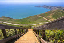 Stairs Descending From The Top Of Hawk Hill; Beautiful Views Of The Green Hills And Shoreline Of Marin Headlands In The Background; North San Francisco Bay Area, California