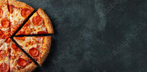 Poster Pizzeria Tasty pepperoni pizza and cooking ingredients tomatoes basil on black concrete background. Top view of hot pepperoni pizza. With copy space for text. Flat lay. Banner