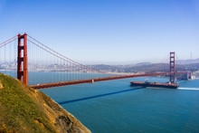 Cargo Ship Passing Under Golden Gate Bridge On A Sunny Day; San Francisco Skyline In The Background; California