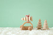 Wooden car carrying a christmas tree in front of pastel background.