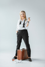 Attractive Fashionable Girl Smoking Cigar While Standing On Grey With Vintage Travel Bag, Newspaper And Glass Of Whiskey