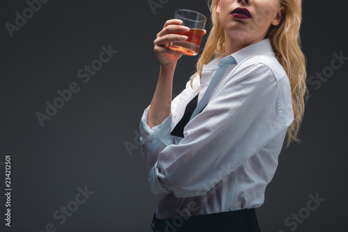 Fotografie, Obraz  cropped view of girl in formal wear holding glass of cognac, isolated on dark gr