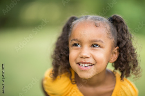 Foto  Cute mixed race little girl laughing and smiling.