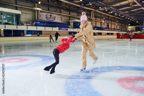 Full length portrait of little girl learning to figure skate with mother in indoor skating  rink, copy space