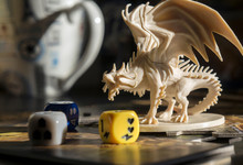 Playing  Board Game, Role Playing Game, Tabletop Games. Figure Of Dragon, Dices. Board Games. Blurred Background.