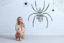 Young Woman Sitting On The Floor And Looking On Imaginary Spider.