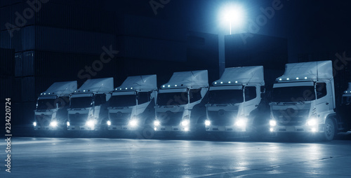 New truck fleet in the container depot at night in blue tone for transportation industry logistics background Canvas Print