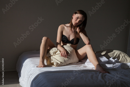 Photographie  woman in underwear sitting on the bed in the bedroom, portrait