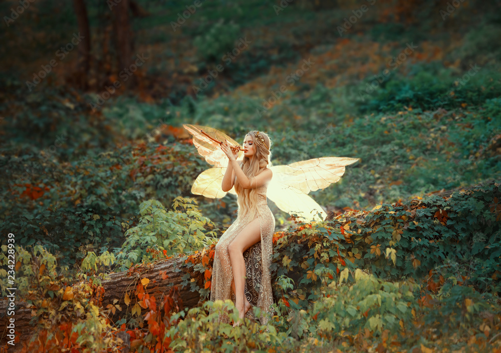 Fototapeta lovely girl druid with blond long hair, sits on a fallen tree, dressed in a gorgeous beige dress with open sexy slim legs, transforming into a light forest butterfly, flashing on a wooden pipe alone