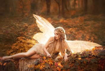 Obraz na Szkleslim girl became a fairy, a model with blond long hair and golden wreath on leaves in the forest in a beige long dress with bare legs, has glowing wings behind her back, atmospheric autumn art photo