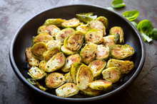 Roasted Brussel Sprouts In Black Bowl Over Slate