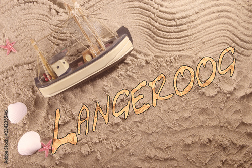 Schriftzug Langeroog im Sand mit Kutter und Muscheln