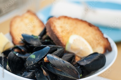 black mussels with crispy bread on a plate