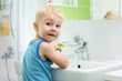 child boy washing his face and hands with soap in bathroom