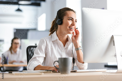 Fotografía  Emotional business woman in office callcenter working with computer wearing headphones