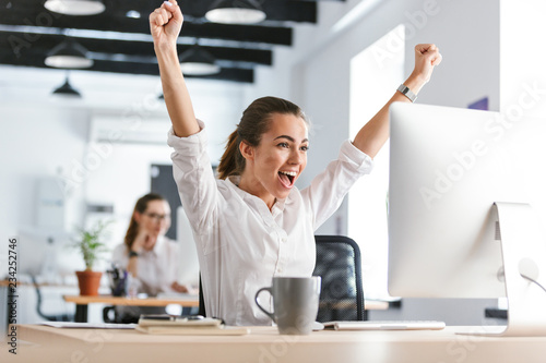 Happy excited business woman in office working with computer make winner gesture.
