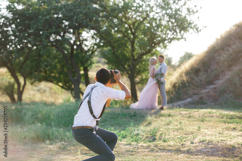 Fotografie, Obraz  wedding photographer takes pictures of bride and groom