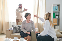 Frowning Family Psychologist In Glasses Sitting In Armchair And Listening To Quarrel Of Couple While Asking Young Lady To Stop Conflict, Emotional Couple Gesturing Hands And Blaming Each Other For