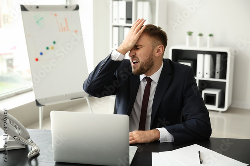 Photo  Emotional young businessman after making mistake while working with laptop in of