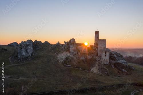 Plakat ruiny średniowiecznego zamku o zachodzie słońca Olsztyn
