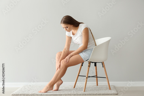 Fotografia  Woman suffering from pain in leg while sitting on chair near light wall