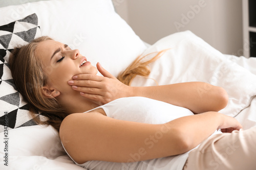 Fotografia  Young woman suffering from toothache while lying in bed