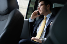 Young Businessman Sitting On Back Seat Of The Car, While His Chauffeur Is Driving Automobile.