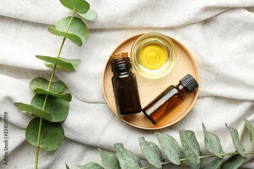Fototapeta Bowl and bottles of eucalyptus essential oil on light cloth