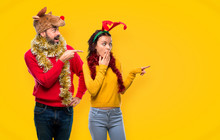 Couple Dressed Up For The Christmas Holidays Pointing Finger To The Side With A Surprised Face On Yellow Background